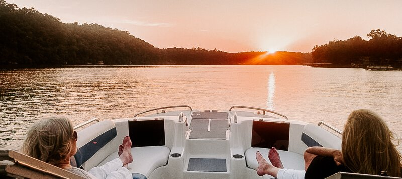 Friends watching sunset on a deck boat